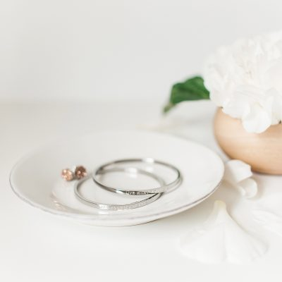 silver bangles in a white jewellery dish next to white petals