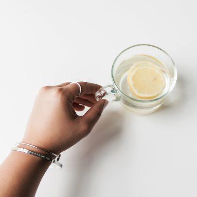 hang holding lemon tea wearing silver bangles