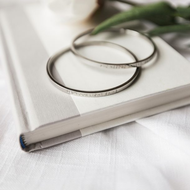 silver quote bangles laying on a white book