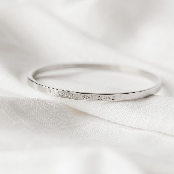 close up of let your light shine silver bangle on white material