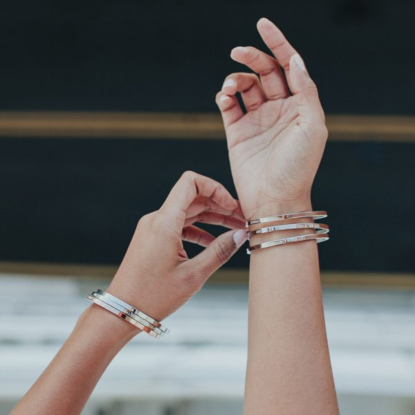 two hands wearing many bangles