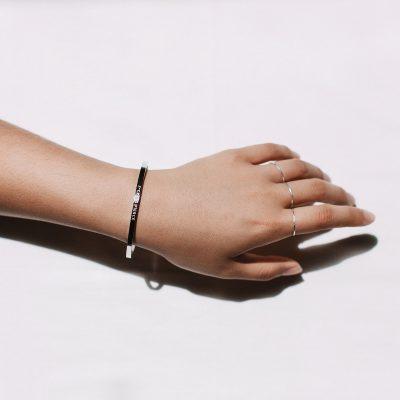 womens hand wearing silver jewellery