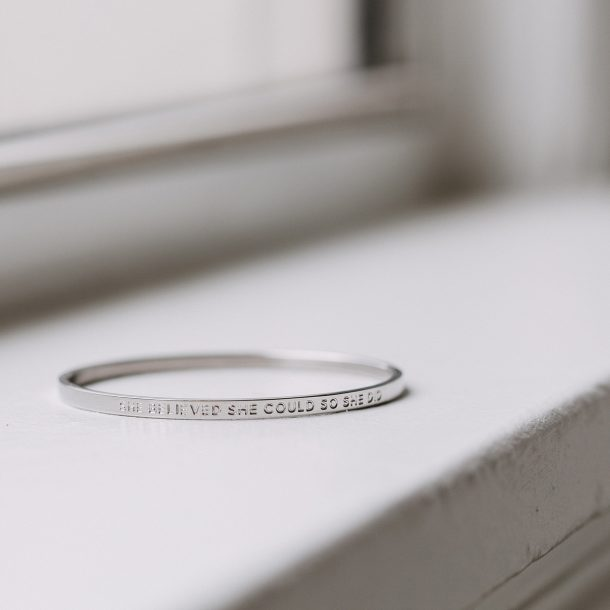 silver inspirational quote bangle near window
