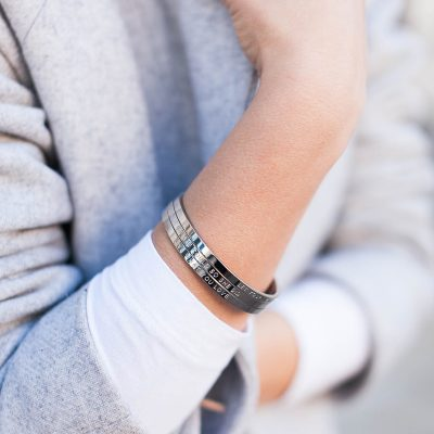 women in grey jacket wearing silver inspirational quote bangles