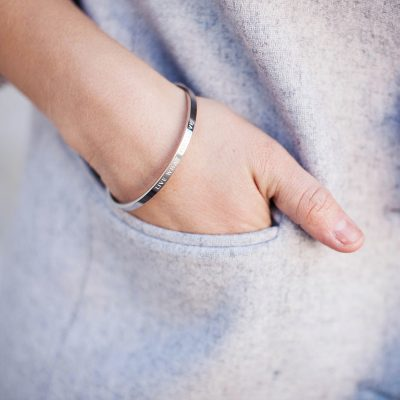 womens hand in grey coat pocket wearing a silver quote bangle