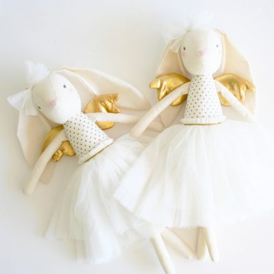 two alimrose gold angel bunny dolls laying next to eachother on a white table