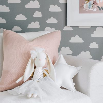 a alimrose gold angel bunny doll with white skirt and bow with gold wingssitting on couch with cloud wallpaper background