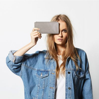 blonde holding Status Anxiety Light Grey Dakota Wallet to her face