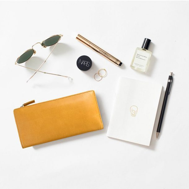 styled flat lay of Status Anxiety Tan Dakota Wallet and bag contents