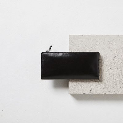 Status Anxiety Black Dakota Wallet on a cement block styled shot