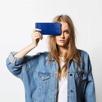 women holding STATUS ANXIETY Status Anxiety Royal Blue Dakota Wallet to her face