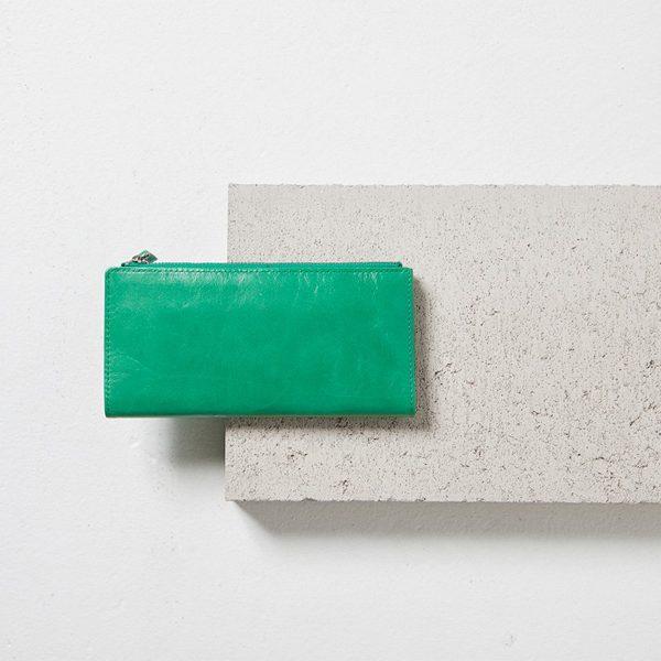 Status Anxiety Emerald Dakota Wallet styled image on a cement block
