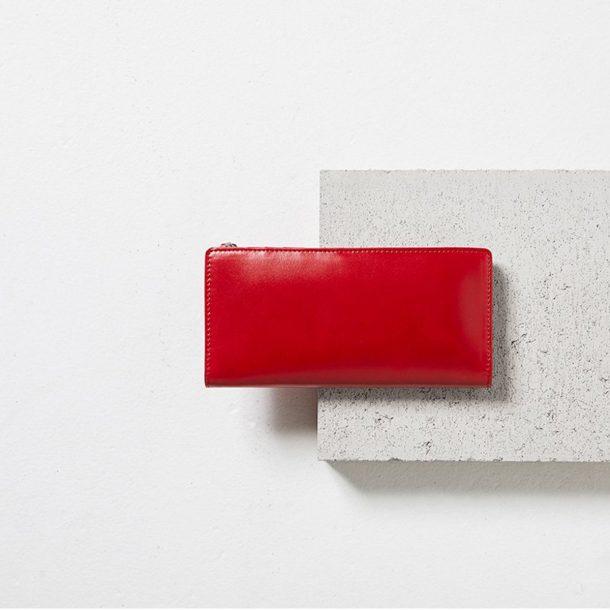 Status Anxiety Red Dakota Wallet on cement block