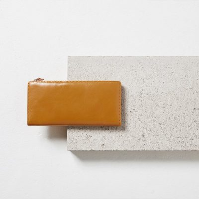 Status Anxiety Tan Dakota Wallet on cement block styled shot