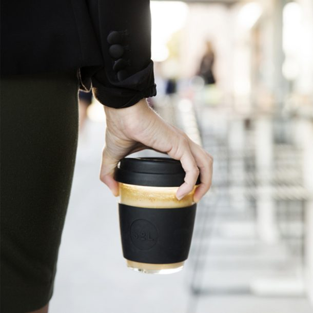 women in business suit holding a glass reusable coffee cup at the airport Basalt Black SoL Cup