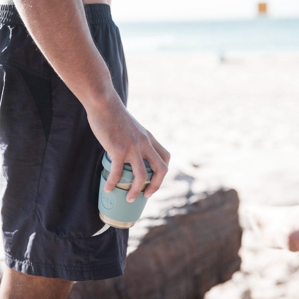 man holding a Gemma Grey SoL Cup at the beach