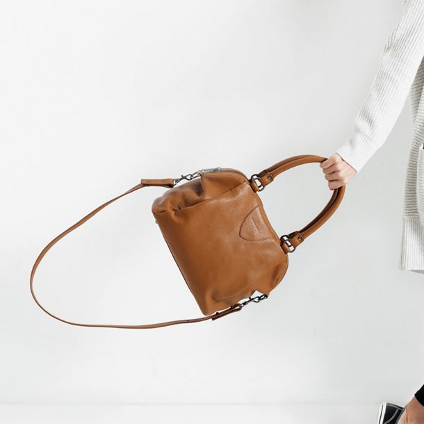 lady swinging a Status Anxiety Tan Force of Being Bag