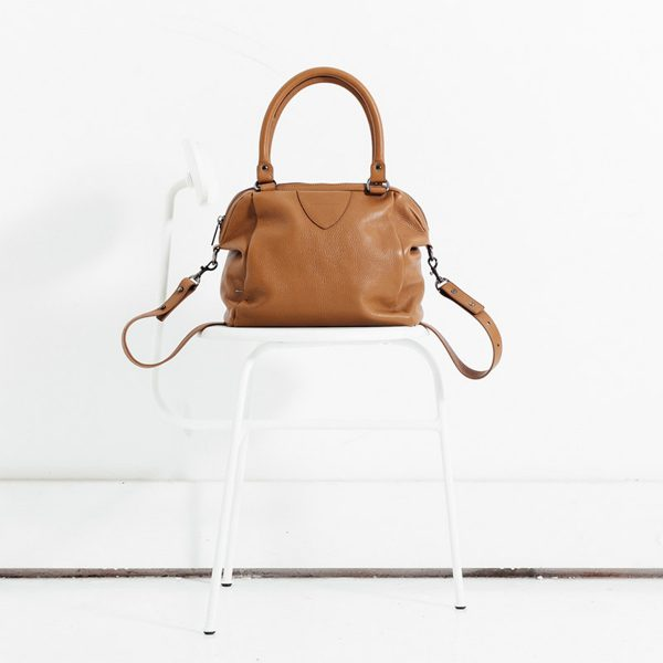 Status Anxiety Tan Force of Being Bag sitting on a white chair
