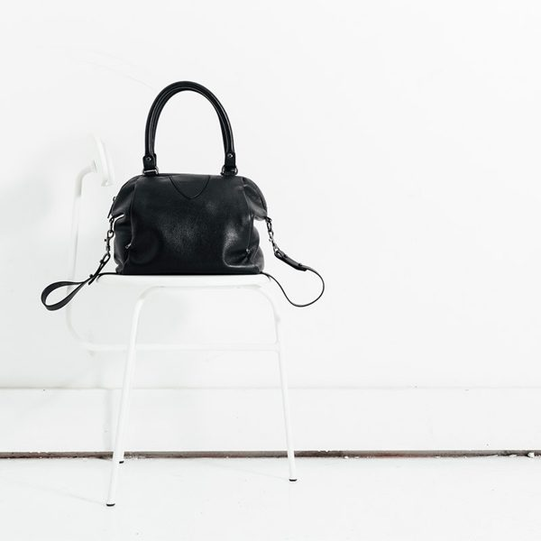 Status Anxiety Black Force of Being Bag sitting on a white chair