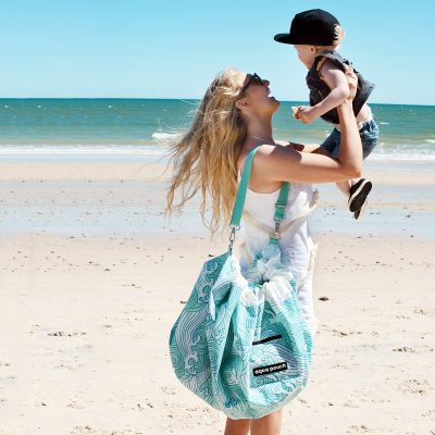 women holding child on beach with a Aqua Waterproof Play Pouch