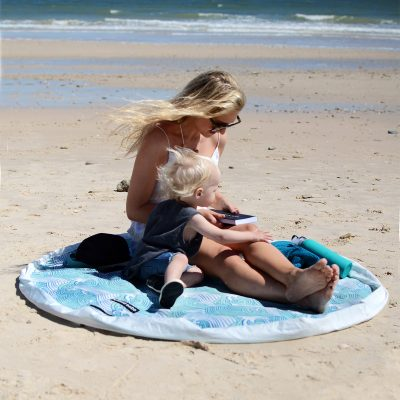 women with child on the beach reading on a Aqua Waterproof Play Pouch