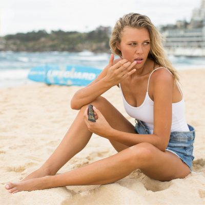 model on the beach applying Bondi Kiss to her lips