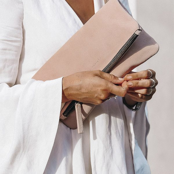 women in white holding Status Anxiety Dusty Pink Feel The Night Clutch