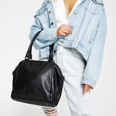 women in denim jacket holding Status Anxiety Black Force of Being Bag