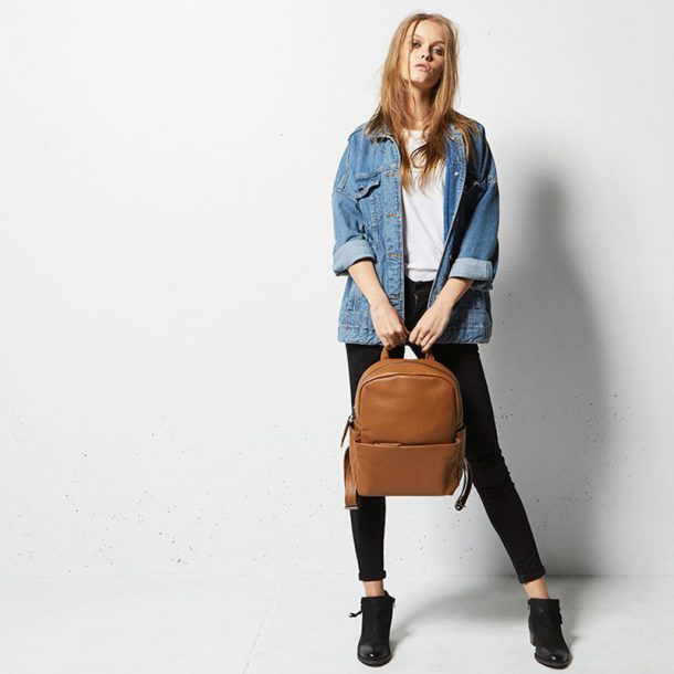 model in denim holding a Status Anxiety Tan Backpack