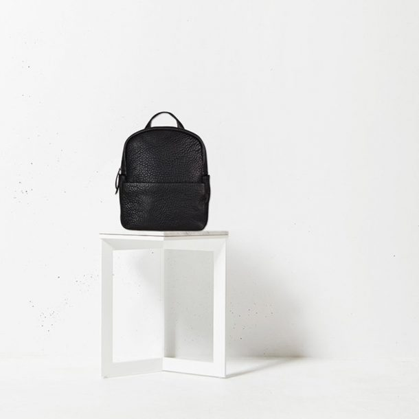 Status Anxiety Black Bubble Backpack on white stool